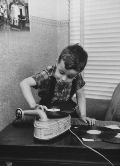 vintage young boy putting record onto turntable