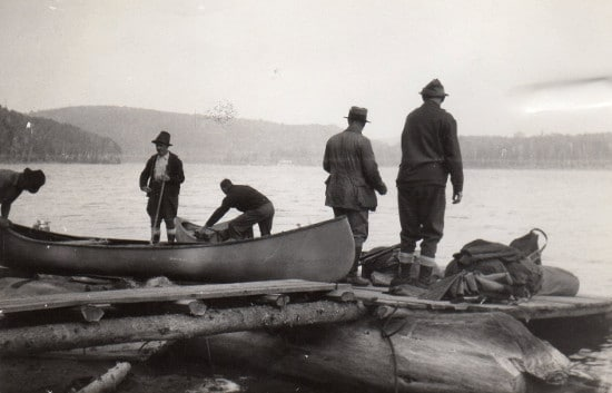 vintage men on canoe trip on beach of lake