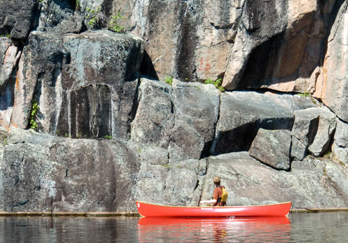 red canoe on lake in front of cliff face bwca
