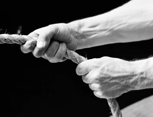 Man holding tightly onto rope close up black white photo.