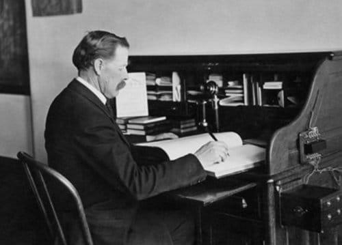 Vintage CEO manager businessman writing in ledger at desk.
