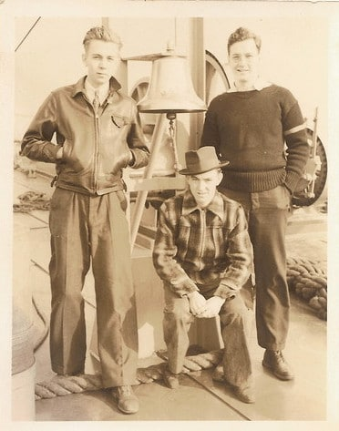 Vintage young men posing in front of bell.