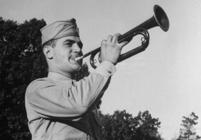 Vintage solider playing trumpet bugle in uniform.