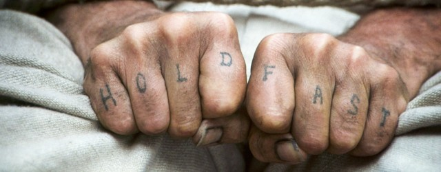 Hold fast written on man's knuckles close up hands.
