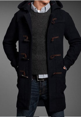 duffle coat unbuttoned over sweater and jeans
