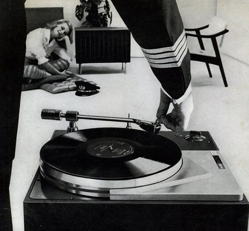 Women sitting on floor listing music a man in uniform hand was adjusting gramophone record.