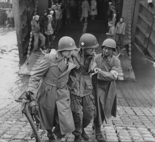 Combat medic helping and carrying injured soldier.