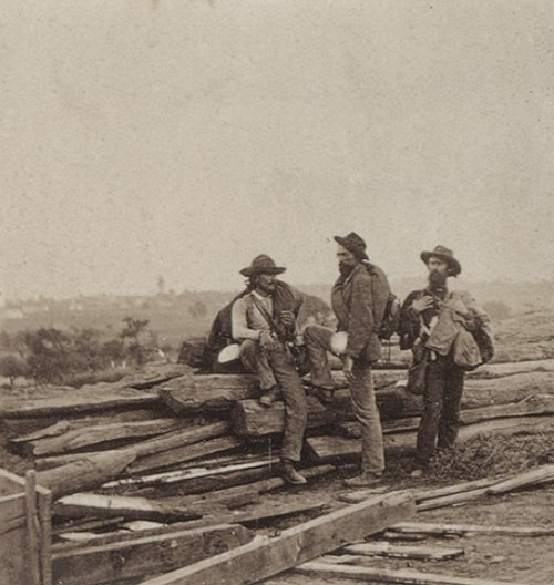 Confederate soldiers standing around broken down building in civil war.
