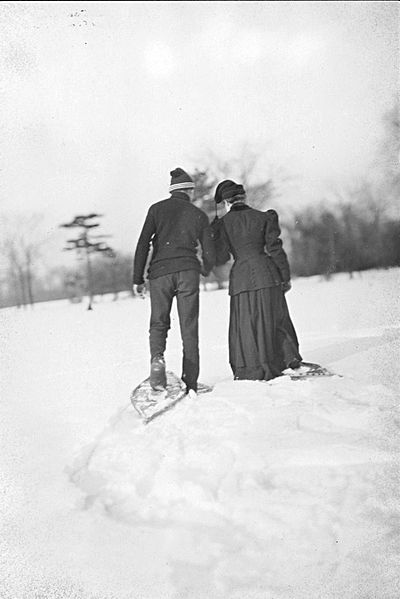 Vintage man and women on date in snow wearing snow shoes.