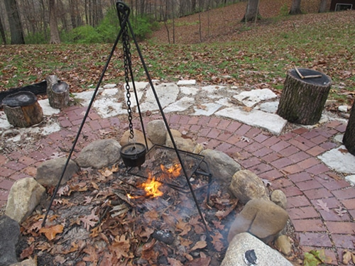 Outdoor fire pit with pot for boiling water.