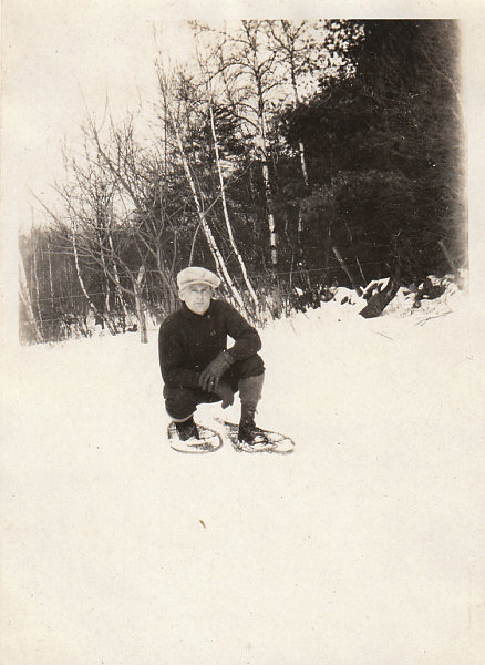 vintage man in snowshoes kneeling in snow