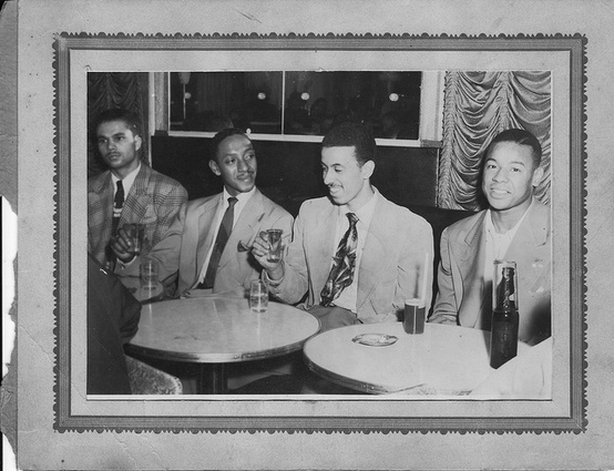 Vintage African American black friends sitting at table talking hanging out.
