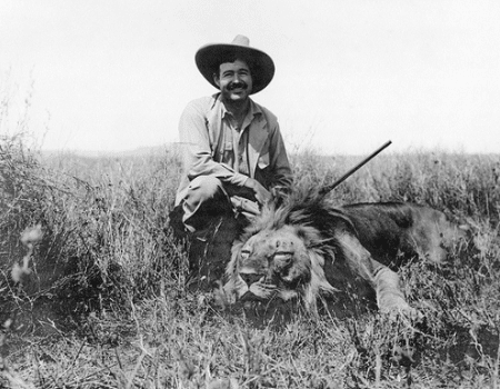 Young Ernest Hemingway smiling with dead lion gun in hand.