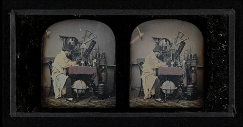 vintage scientist at table with large microscope
