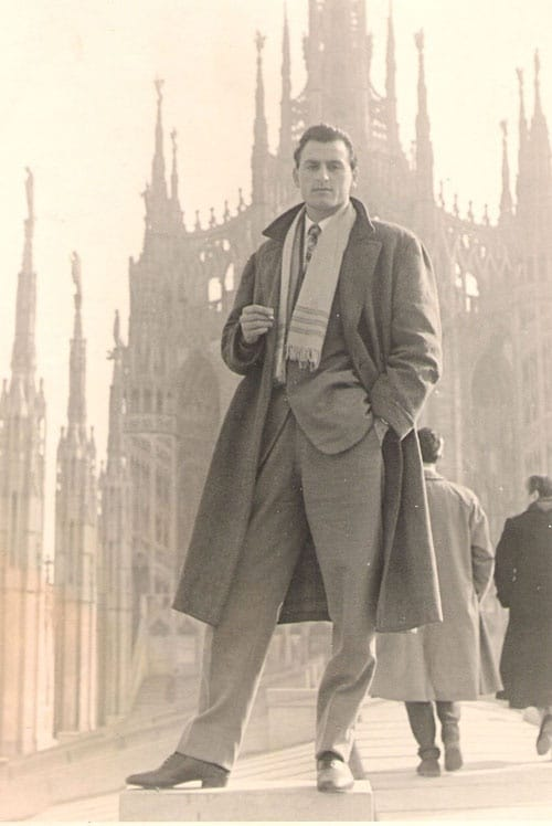 Vintage man in Europe wearing long overcoat outside cathedral.