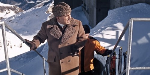 james bond villain wearing astrakhan hat and brown overcoat