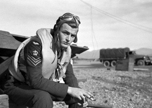 vintage wwii pilot sitting in uniform smoking cigarette aviator cap