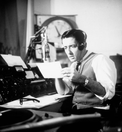 Vintage man doing podcast wearing headphones.