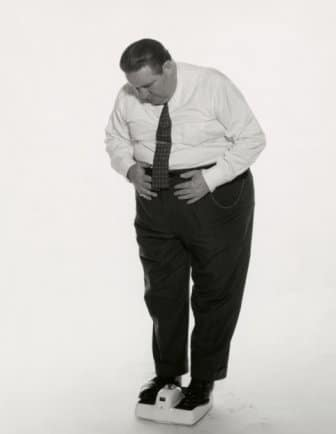 Vintage overweight man standing on weight scale.