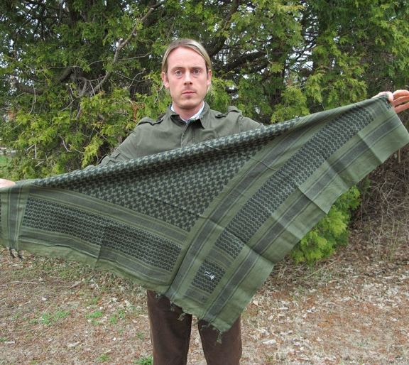 Man fold scarf into triangle.