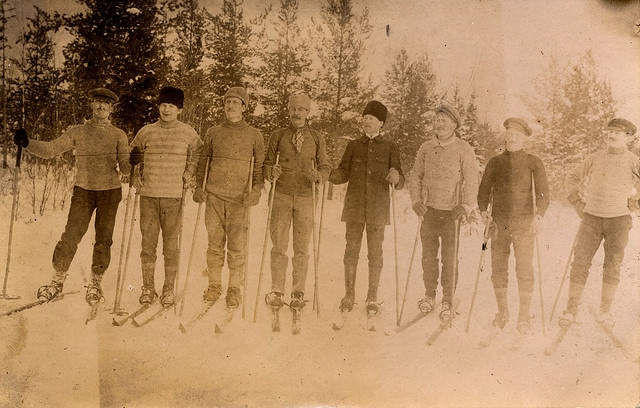 Vintage skiers group of men on skies in woods.
