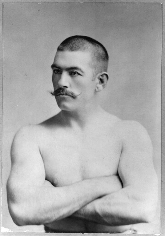 Vintage boxer posing for portrait arms crossed mustache.