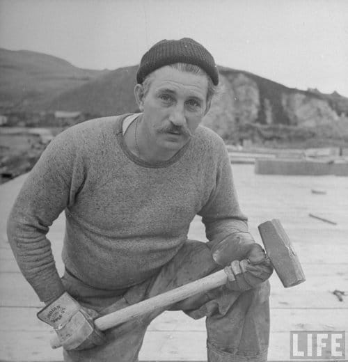 Vintage man with sledgehammer wearing stocking watch cap.