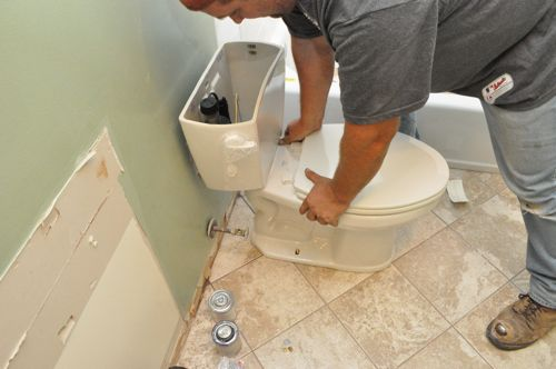 how to install a new toilet firmly pressing toilet onto floor