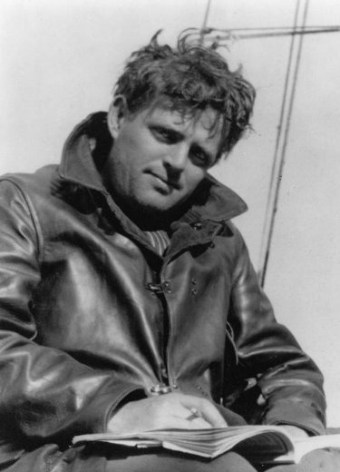 Jack London in leather jacket sitting outdoor writing in notebook with ruffled hair.