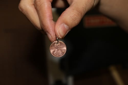 small jump ring through hole in penny for diy charm bracelet
