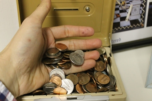 hand sorting through coin bank