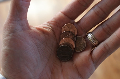 variety of pennies in man's hand