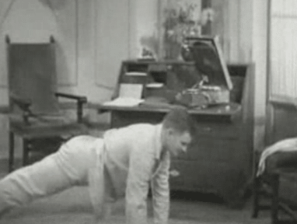 vintage man in suit doing pushups in living room