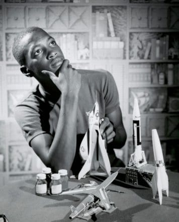 Vantage young man with model rockets staring off in thought.