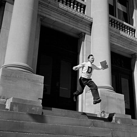 vintage young man running down stairs with diploma