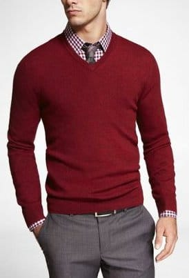 red sweater layered over checkered long sleeve shirt and tie
