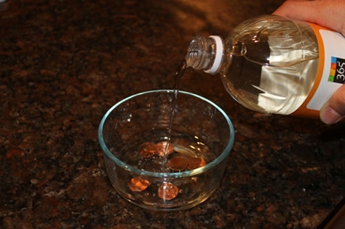 pennies in bowl with vinegar cleaning coins