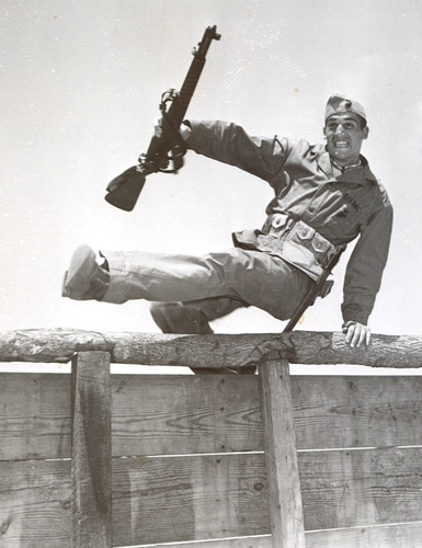Vintage soldier jumping wooden fence basic training.