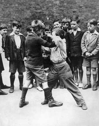 Vintage boys fighting at school ring of onlookers audience.