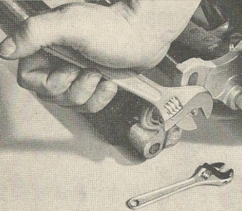 Vintage man using wrench close up.