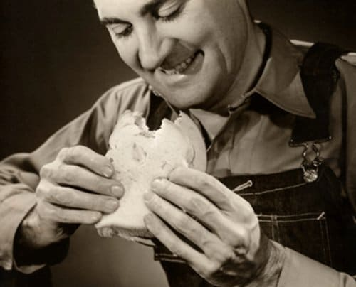 vintage man eating sandwich smile on face