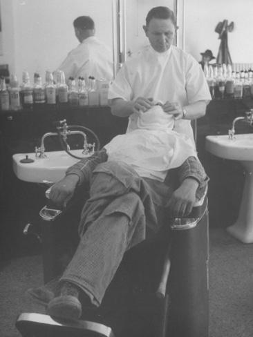 Vintage barbershop man with hot towel on face.