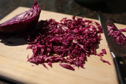 Vintage chop red cabbage into thin slices.