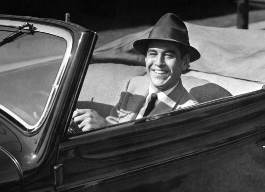 Vintage man in convertible smiling wearing hat.