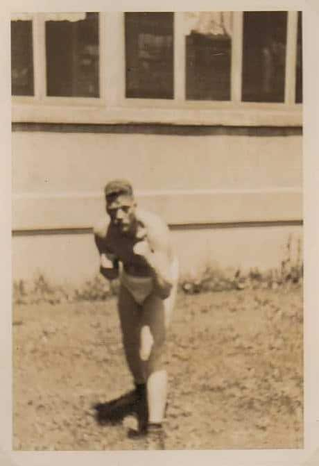 vintage man in underwear outside house in boxing fighting pose