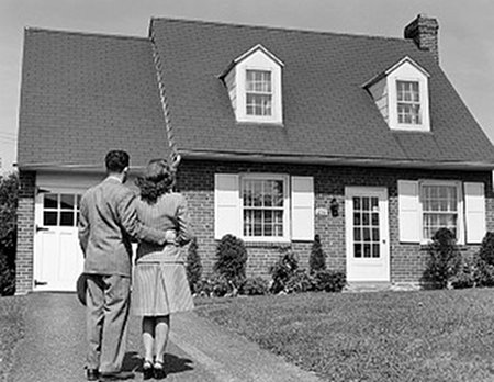 Vintage couple looking at new home standing in driveway.