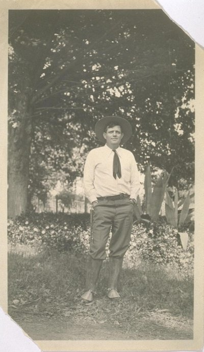 jack london standing outdoors with hat and short tie