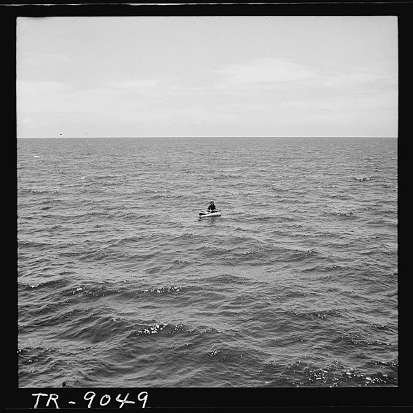 vintage man in a liferaft in middle of ocean
