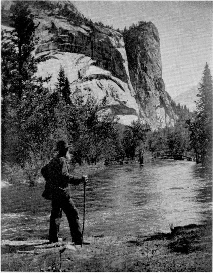 John Muir standing by river and canyon with walking stick.