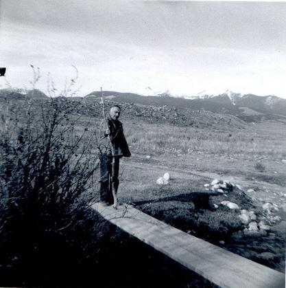 elderly old man walking with stick across wooden bridge in mountains